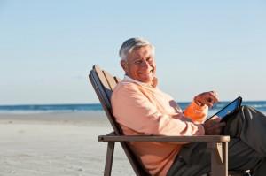 Senior man on beach using digital tablet